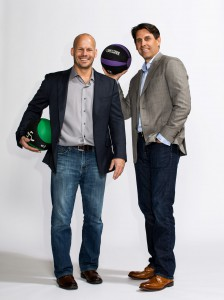 Anytime Fitness co-founders Dave Mortensen and Chuck Runyon standing and smiling with medicine balls wearing business casual attire. View larger image.