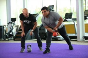 Coach and trainee working out with a kettle bell