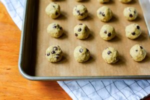 mini cookie dough balls on a cookie sheet